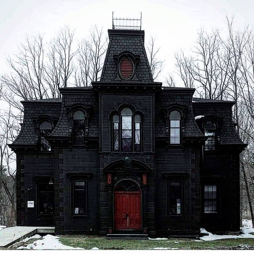 Dark Victorian house with red door